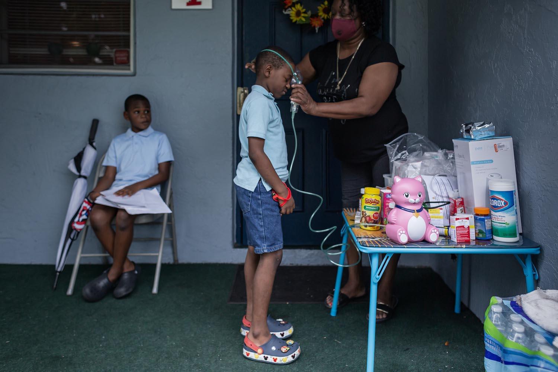 Thelma Freemanは、孫のJayceonにネブライザーを装着する方法を示しています。 フリーマンの他の孫ドノバンも着席しており、ネブライザーを使用しています。 トーマスコーディ/パームビーチポスト